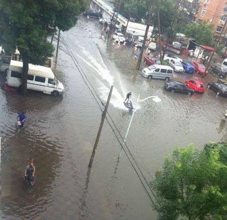Ein Mann fährt auf einem Wasserjet durch eine überflutete Stadt.