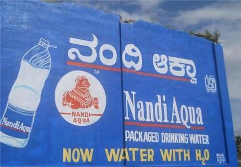 """Auf einer Werbung für Trinkwasser steht """"Now water with H2O""""."""