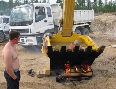 Auf einer Baustelle wurde eine Baggerschaufel zu einem Pool umfunktioniert. Durch ein Feuer unter der Schaufel wird das Wasser sogar erwärmt.