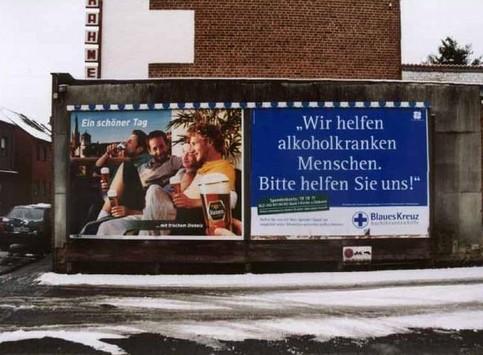 """Ein Schild """"Wir helfen alkoholkranken Menschen"""" neben einer Werbung für Bier."""