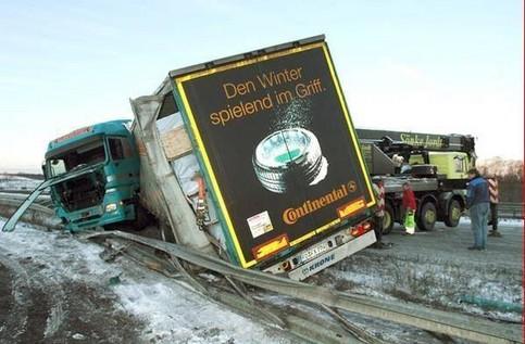 Ein LKW, auf dem Werbung für Winterreifen prangt, hat einen Unfall auf einer winterlichen und schneereichen Straße.