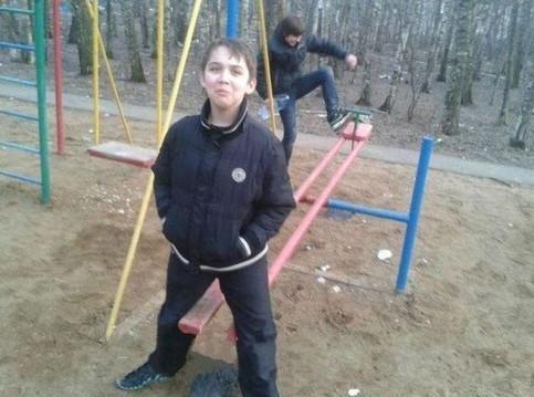 Ein Junge steht mit gespreizten Beinen über dem Ende einer Wippe. Er lacht in die Kamera, während am anderen Ende der Wippe ein anderer Junge auf die Wippe treten will.