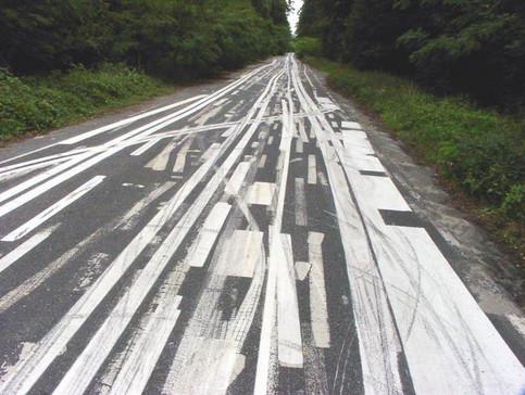 Eine Straße, auf der mehrere Markierungen durcheinander angebracht wurden.