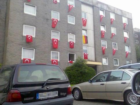 Ein Haus, aus dessen Fenstern viele Türkische Fahnen hängen, aber nur eine Deutsche.