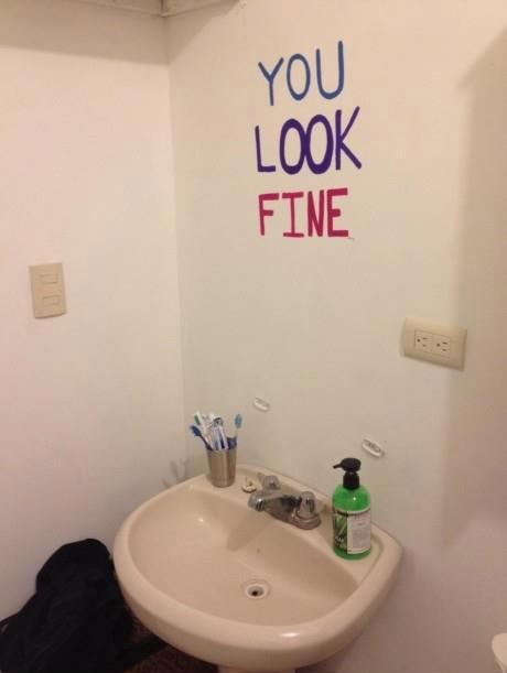 """Über einem Waschbecken hängt kein Spiegel, stattdessen steht an der Wand """"You look fine""""."""