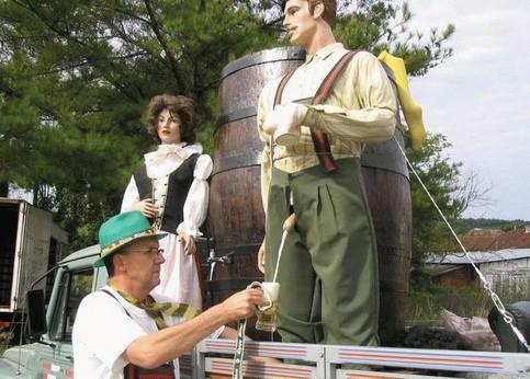 Ein Mann zapft Bier aus dem Hosenlatz einer Plastikfigur.