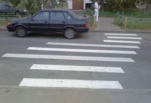 Ein Zebrastreifen ist schief und krumm auf eine Straße gemalt.