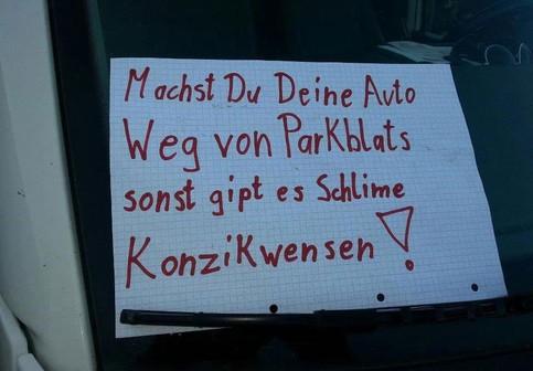 """Hinter dem Scheibenwischer eines Autos hängt ein Zettel """"Machst Du Deine Auto Weg von Parkblats sonst gipt es Schlime Konzikwensen!"""""""