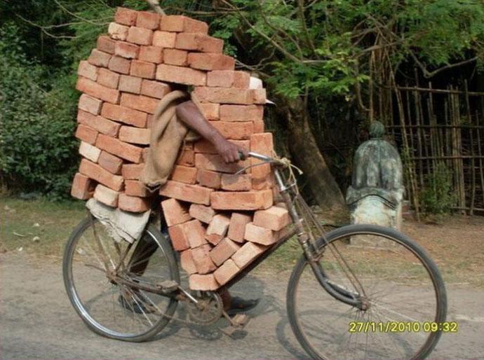 Ein Mann transportiert eine große Menge Ziegelsteine auf einem Fahrrad.