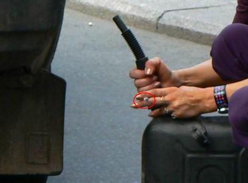 Eine Frau öffnet mit einer Zigarette in der Hand einen Benzinkanister
