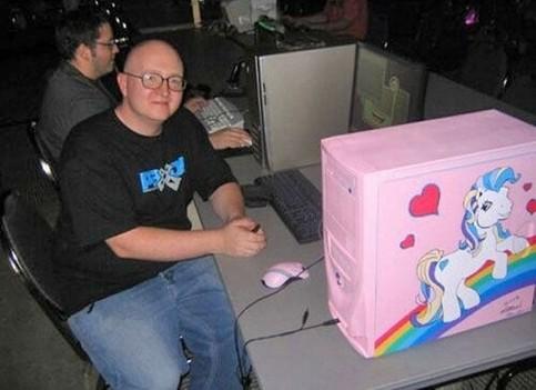 Ein Mann hat einen PC auf einer LAN-Party, der rosa bemalt ist und auf dem Herzchen und süßes Pferd gemalt sind.