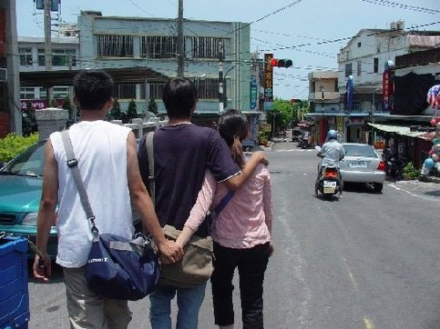 Ein Liebespaar geht spazieren. Der Freund hat seinen Arm um die Freundin gelegt. Diese hält heimlich hinter dem Rücken ihres Freundes Händchen mit einem anderen Mann.